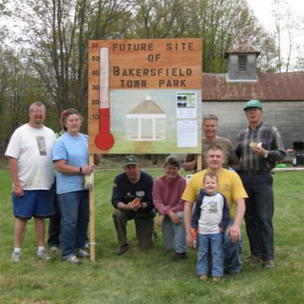 Photo of people posing around a sign reading: Future Site of Bakersfield Town Park.