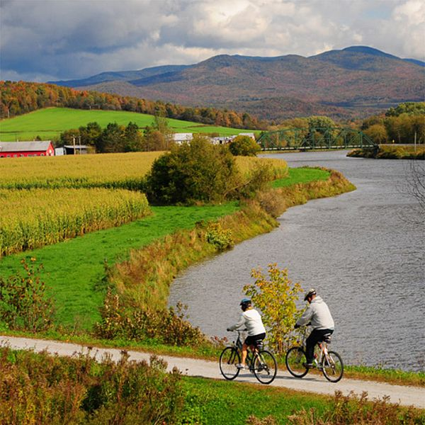 Photo of bicyclists on a rec path surrounded by a fall landscape with the Missiquoi River and mountains.