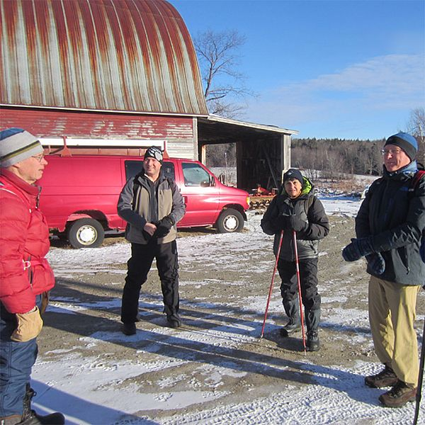 A group of Keeping Track team members gather in a farm driveway in winter.