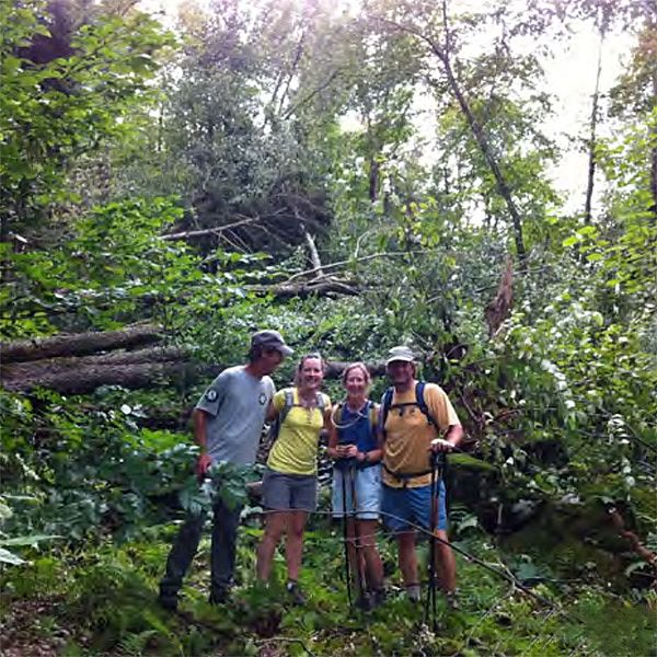 Photo of group of people in front of a pile of trees knocked down by a storm.